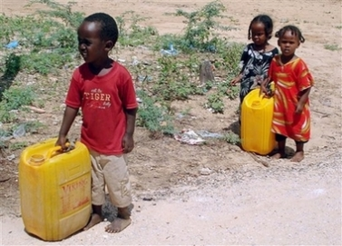 Displaced Somali children carry plastic cans in search of water in a camp outside Mogadishu Saturday, Nov. 17, 2007. A roadside bomb hit a truck carrying soldiers in Somalia's capital Saturday, killing two people and wounding six, a witness said, and an African Union peacekeeping base was attacked in a separate incident . (AP Photo/Abdi Farah Warsameh)